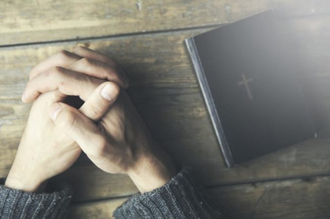 Young man  praying and bible on table